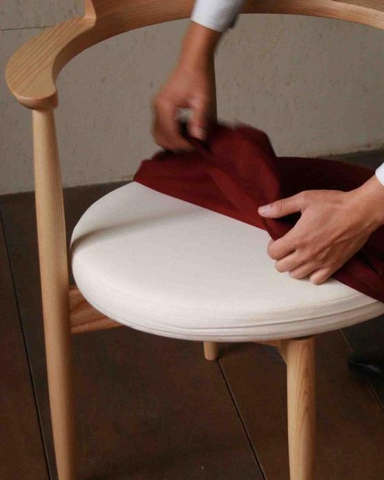 丸くて可愛いホワイトアッシュ材のUZURAチェアのカバーを外している様子:澪工房