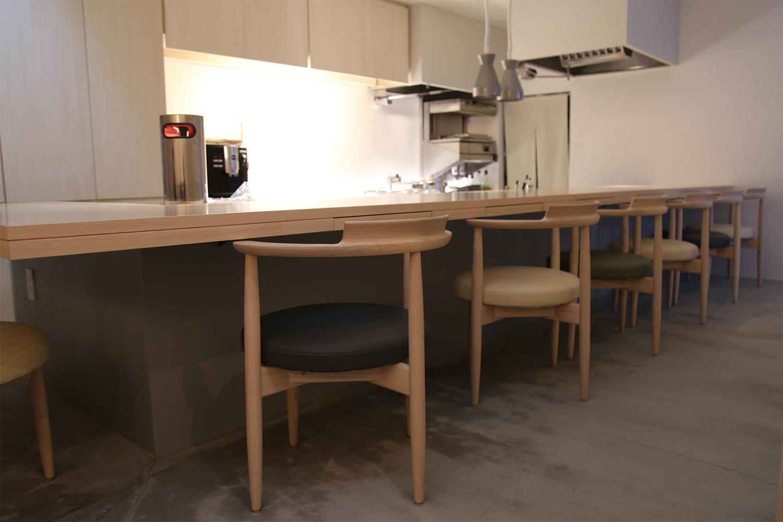 ホワイトアッシュ材のL字型のカウンターとUZURAチェアが置かれたレストラン:澪工房