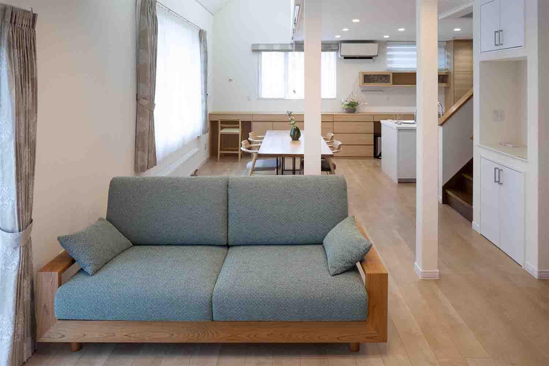 タモ材のキッチン収納棚とナラ材のダイニングテーブルとサクラ材のソファが置かれたリフォーム物件