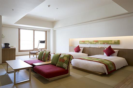 可愛いクッションの座椅子とベッド2台が置いてあるホテルの客室:澪工房