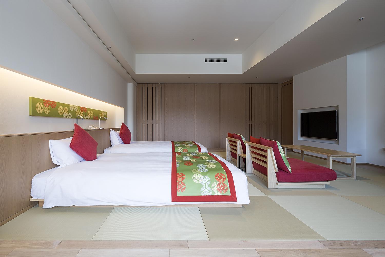 ベッド2台と座椅子が置いてあるホテルの客室:澪工房