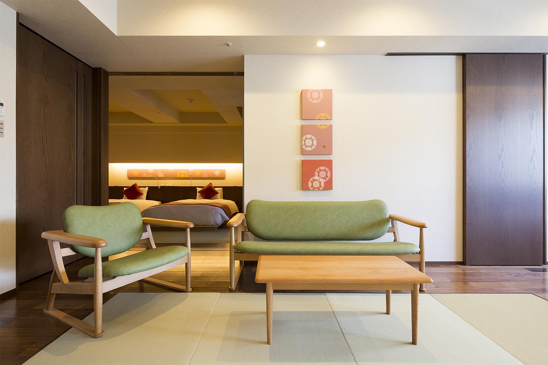 グリーンのMAMEソファとMAMEチェアが置いてあるホテルの客室:澪工房