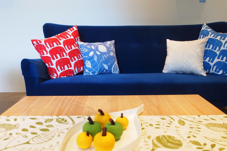 北欧柄のクッションと青いソファ