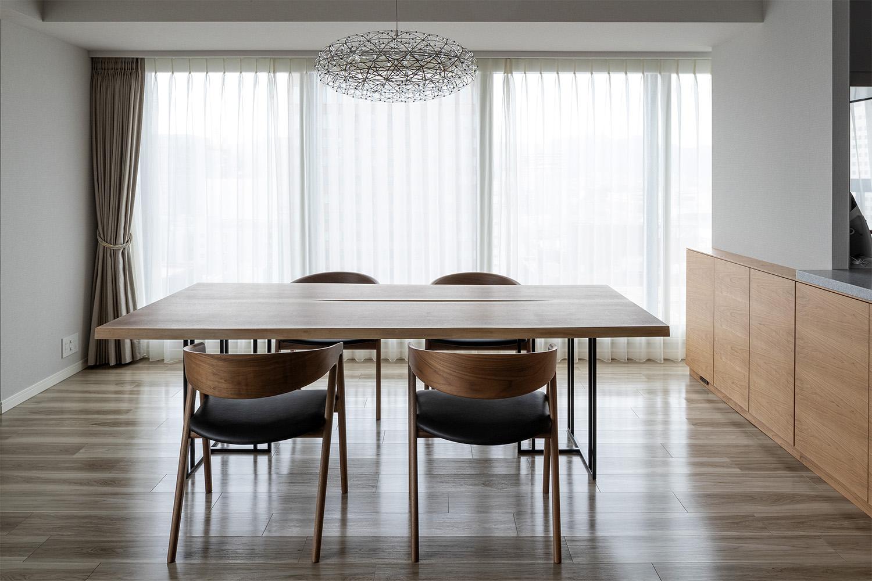 ウォルナット材のダイニングテーブルとHARPチェアが置いてあるマンション:澪工房