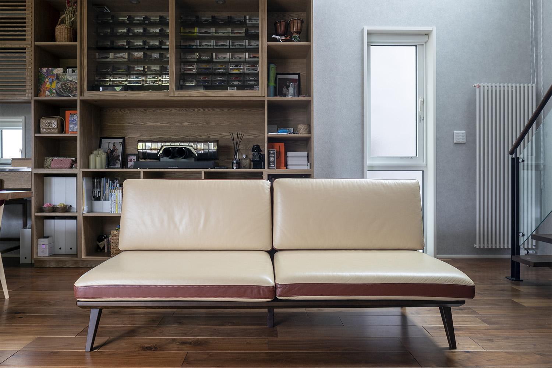 ウォルナット材の床材と2トーンのソファがおしゃれな新築