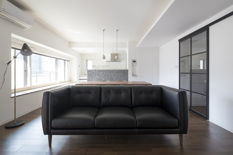 ウォルナット材の床材と黒革のソファがおしゃれなリフォーム物件