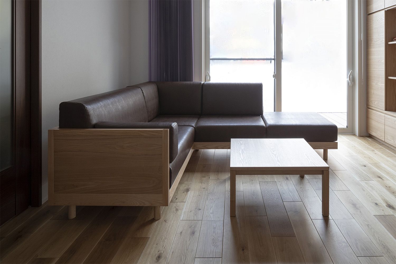 タモ材のL型ソファと正方形のテーブルが置かれた新築