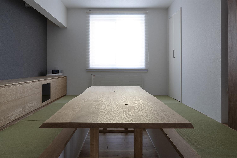 耳付きのタモ材のテーブルと畳ベンチが置かれた新築